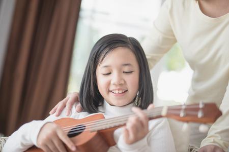 ASian girl playing ukulele wiyh her morther