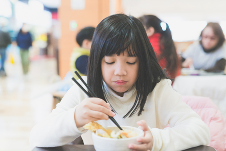 korean salad: Beautiful Asian girl eating Tempura Rice Bowl