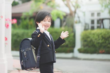 Aziatische student naar school gaan en zwaaien vaarwel