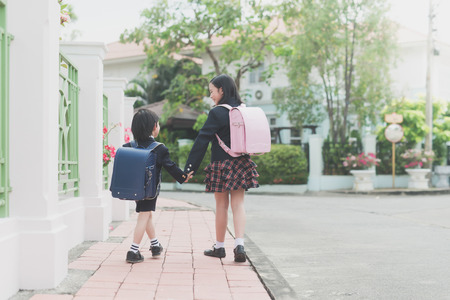 학교에가는 동안 귀여운 아시아 어린이 함께 손을 잡고
