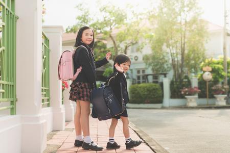 studenti asiatici che vanno a scuola e addio agitando Archivio Fotografico