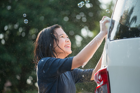 Asian girl washing car in the garden on summer day Фото со стока