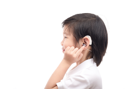Cute Asian child with hearing aid on white background isolated