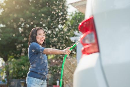夏の日に庭でアジアの少女洗浄車 写真素材 - 74101837