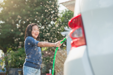 Asian girl washing car in the garden on summer day Reklamní fotografie