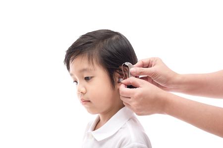 Dokter die gehoorapparaat plaatst in het oor van een jongen