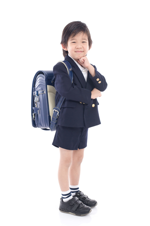 Asian child in school uniform with blue school bag thinking on white background isolated