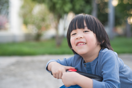 Cute Asian child driving blue toy car outdoors Stok Fotoğraf - 75785818