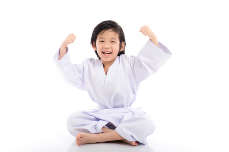 Happy successful winner child in white kimono sitting on white backgroud isolated