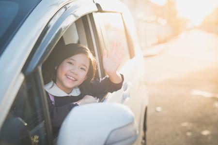 Asiatisches Mädchen in dem Student Uniform mit dem Auto zur Schule zu gehen und zum Abschied winken Standard-Bild - 75784758