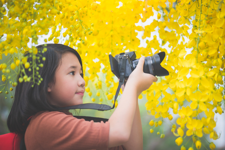 Beautiful Asian girl take photo with blooming yellow flower,Thailand travel concept