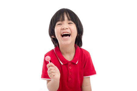 Cute Asian child eating a lollipop on white background isolated Banco de Imagens