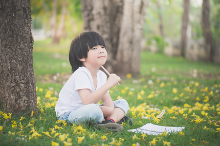 Little Asian boy sitting under the tree and drawing in notebook at park Stock Photo