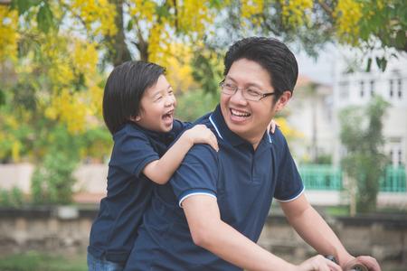 Gelukkige Aziatische vader en zoon fietsen samen met de lente achtergrond