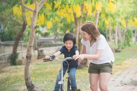 그녀의 귀여운 아들을 자전거를 타고 가르치는 아름답고 행복한 아시아 어머니