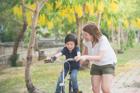 Beautiful and happy Asian mother teaching her cute son to ride a bicycle