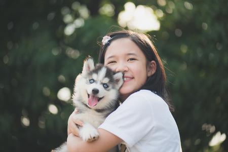 背景のボケ味のある公園でのシベリアン ハスキー子犬と遊ぶ美しいアジアの少女