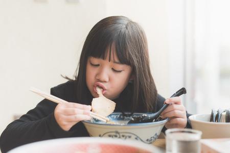 日本食レストランでチャーシュー ラーメンを食べて美しいアジアの少女