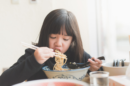 Beautiful Asian girl eating chashu ramen in japanese restaurant Imagens