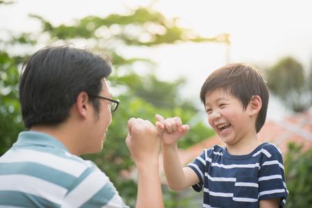 アジアの父と彼の息子の小指を作る、自然の背景上の約束