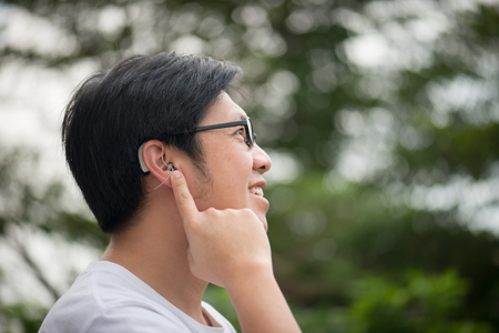 Aziatische man met gehoorapparaat achter het oor buitenshuis
