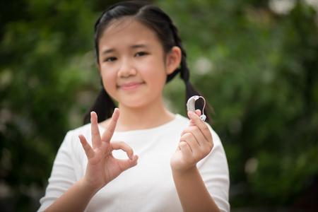 Beautiful asian girl holding hearing aid