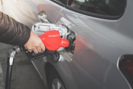 Closeup of Asian man pumping gasoline fuel in car at gas station. Reklamní fotografie