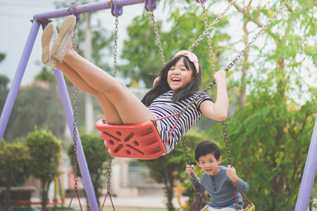 asian children swinging on the playground Stock Photo