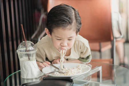 Cute Asian chid eating Spaghetti Carbonara in restaurant,vintage fiter