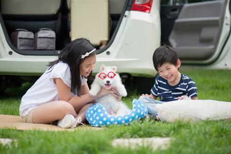 Bambini asiatici che giocano con cucciolo siberiano husky nel parco Archivio Fotografico - 80111786