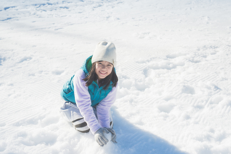 Happy asian girl smiling outdoors in snow on cold winter day Imagens