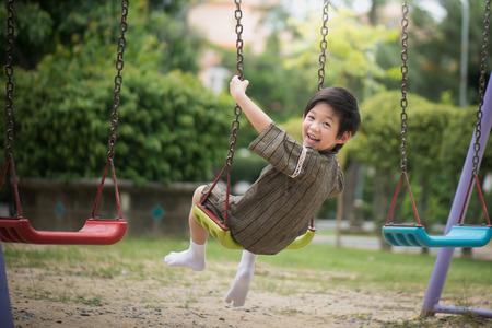 Lindo niño asiático en kimono jugando en columpio en el parque Foto de archivo - 81593984
