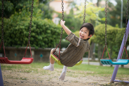Cute Asian child in kimono playing on swing in the park