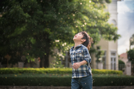 Carino bambino asiatico guardando nel parco sotto la pioggia Archivio Fotografico