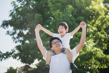 アジアの父と息子が公園で遊んで