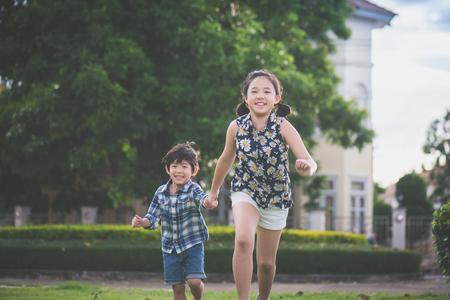 かわいいアジア子供 runing、持株は屋外の公園で一緒にいた