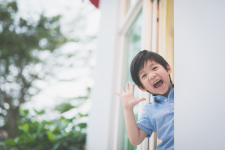 Portrait of cute Asian child at the open window