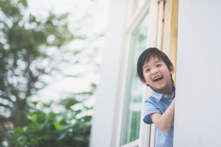 Portret van schattig Aziatisch kind bij het open raam Stockfoto