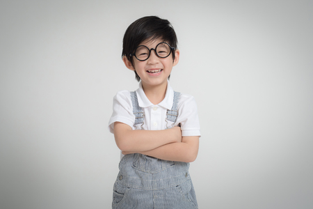 Happy Asian child wearing glasses smiling on gray background