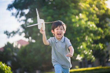 Het leuke Aziatische kind spelen karton vliegtuig in u park buiten Stockfoto
