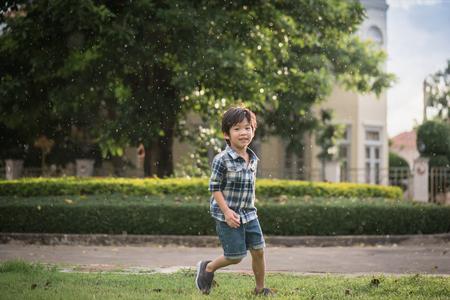 かわいいアジアの子が雨の中公園で遊んで