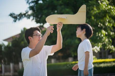 Aziatische vader en zoon spelen karton vliegtuig samen in het park buitenshuis