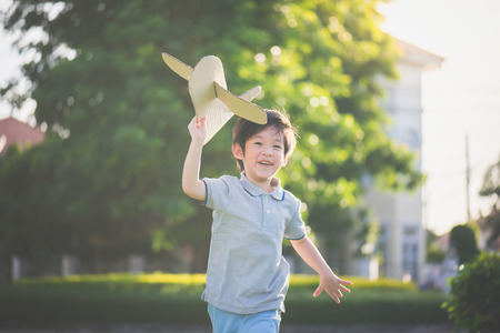 Cute Asian child playing cardboard airplane in thee park outdoors Foto de archivo