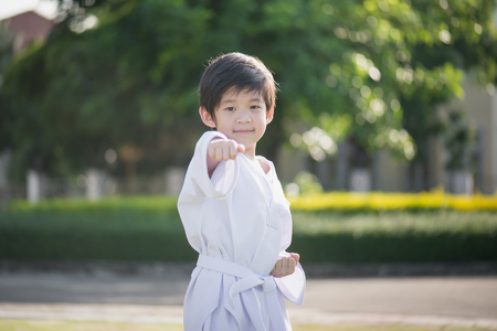 Cute Asian child in white kimono during training karate in summer outdoors Stock Photo