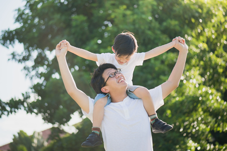 Asian father and son playing in the park Foto de archivo
