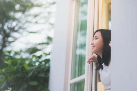 귀여운 아시아 여자의 초상화는 창 밖을 내다 본다.