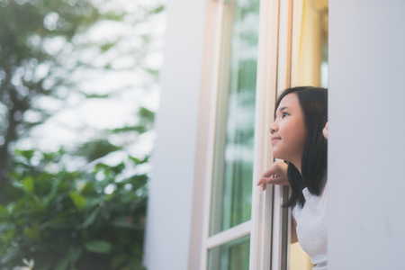 Portrait of cute Asian girl look out the window
