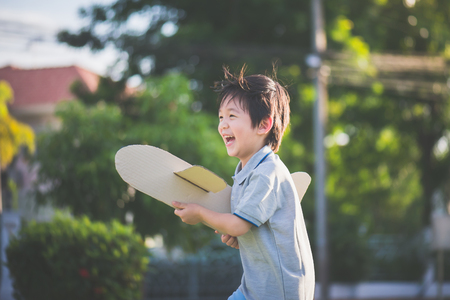 thee: Cute Asian child playing cardboard airplane in thee park outdoors Stock Photo