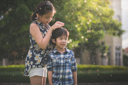 Beautiful Asian girl using hands protect her younger brother from the rain