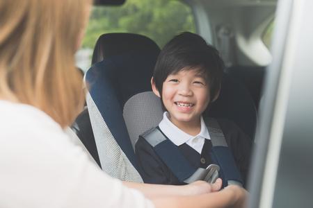 アジアの女性の車の安全シートベルトを持つ子供を固定